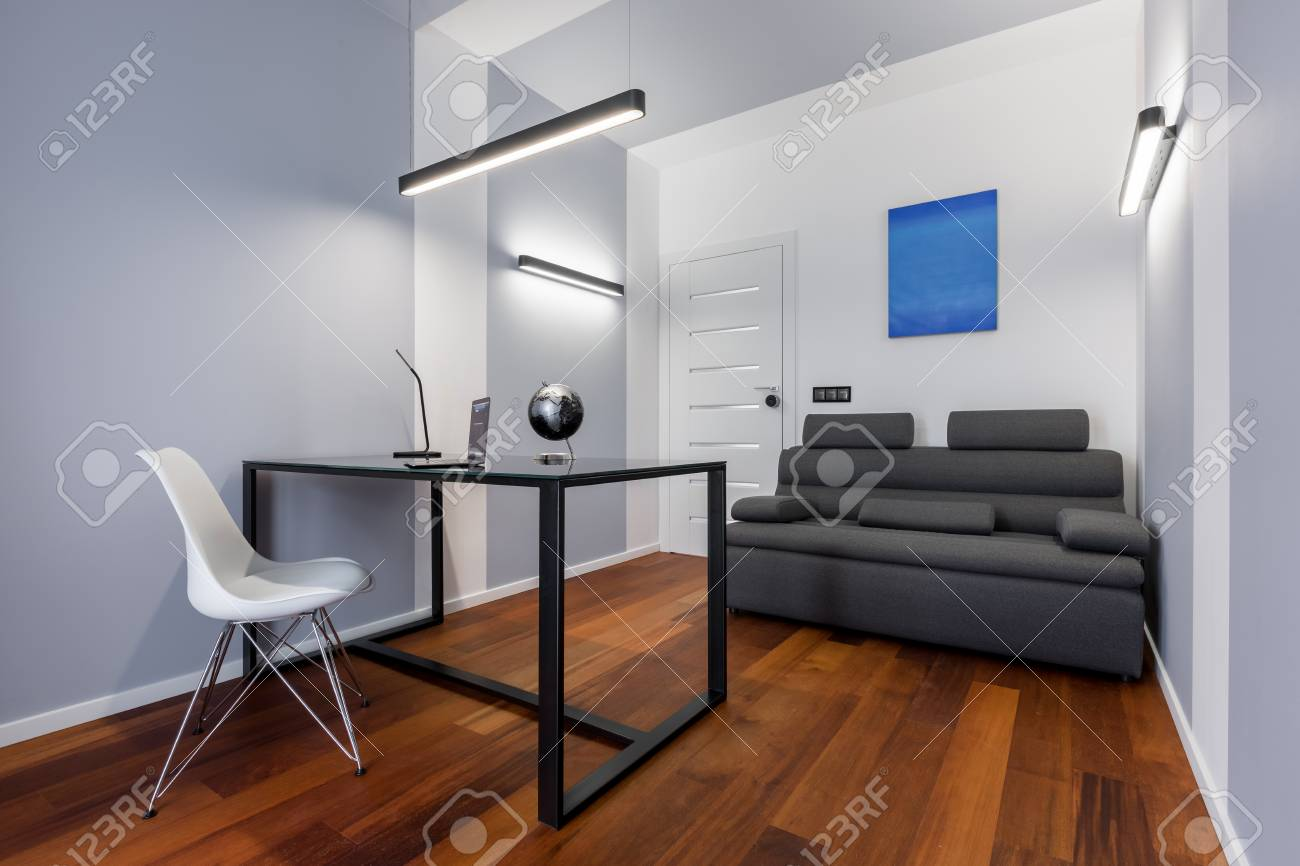 Bureau à domicile blanc avec table noire, chaise blanche et canapé gris