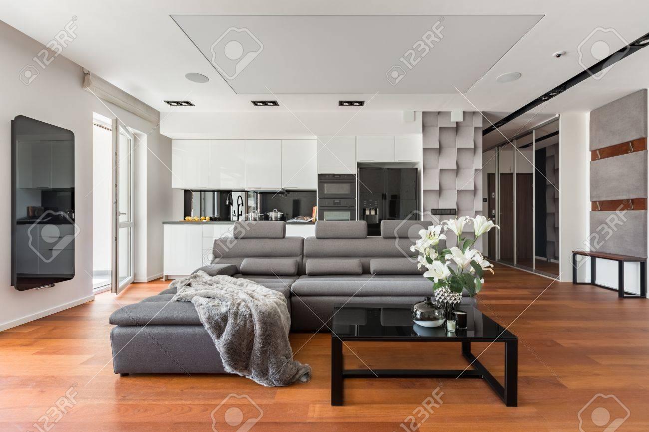 Soggiorno aperto con divano grigio, tavolino da caffè nero e angolo cottura