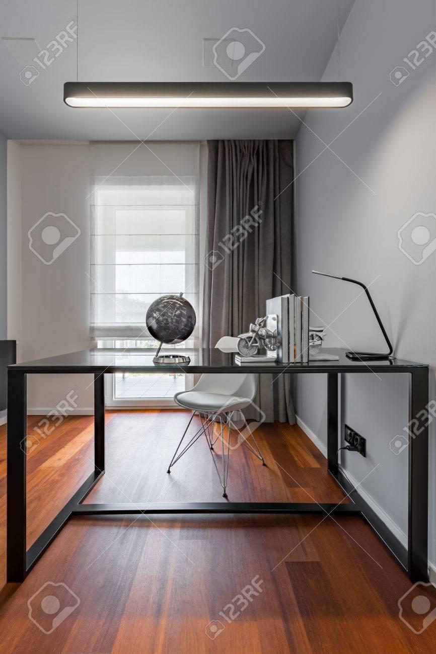 Bureau à la maison avec table noire, lampe simple et chaise blanche