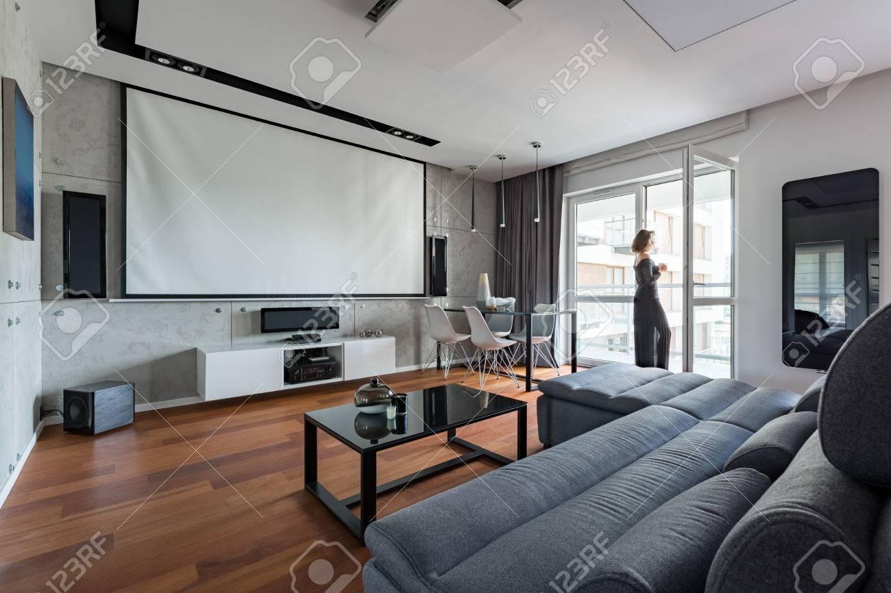 Salon gris et blanc avec canapé, table, balcon et écran de projection