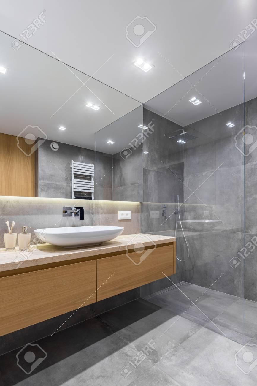 Salle De Bain Grise Avec Long Comptoir, Miroir Et Douche à L ...