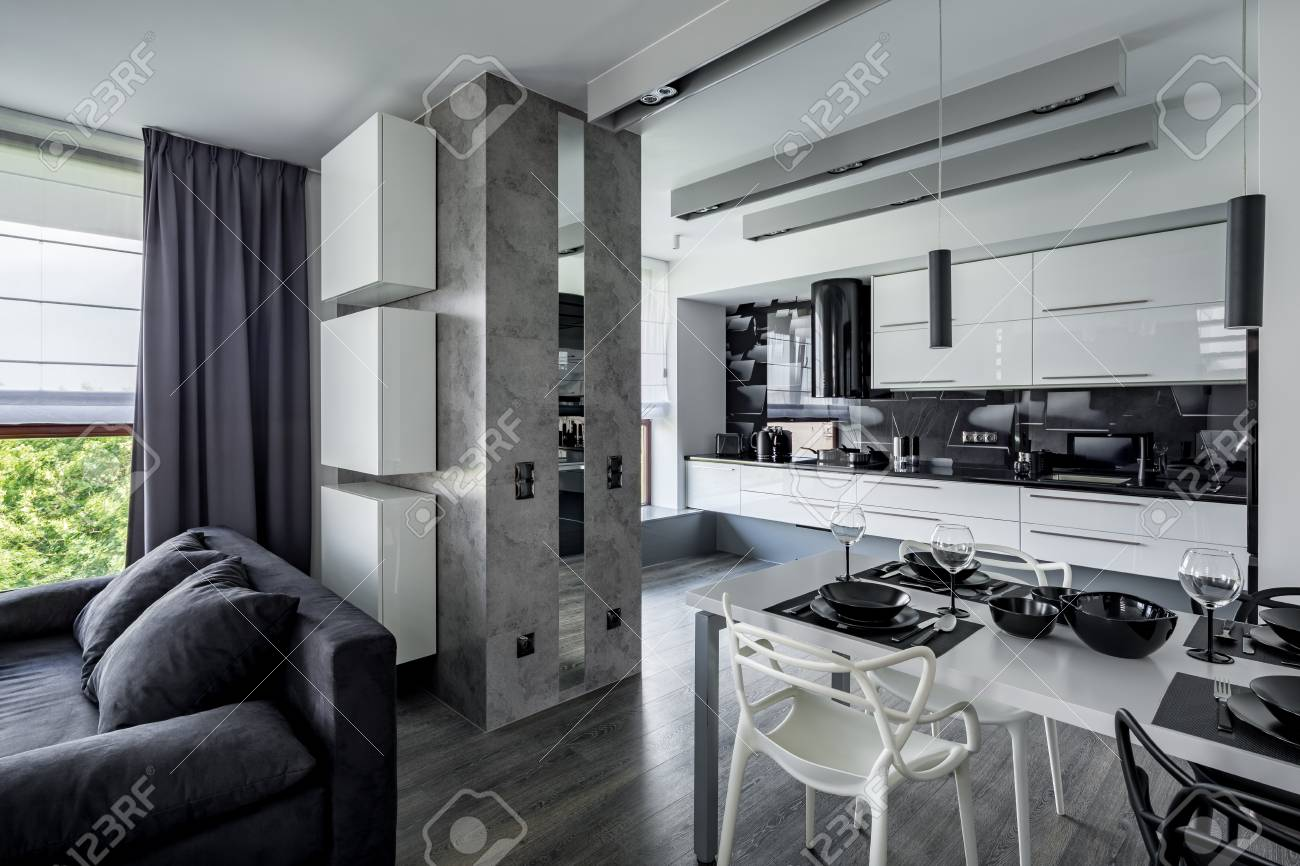 Modern Apartment With Open Kitchen, Dining Table And Sofa Stock ...