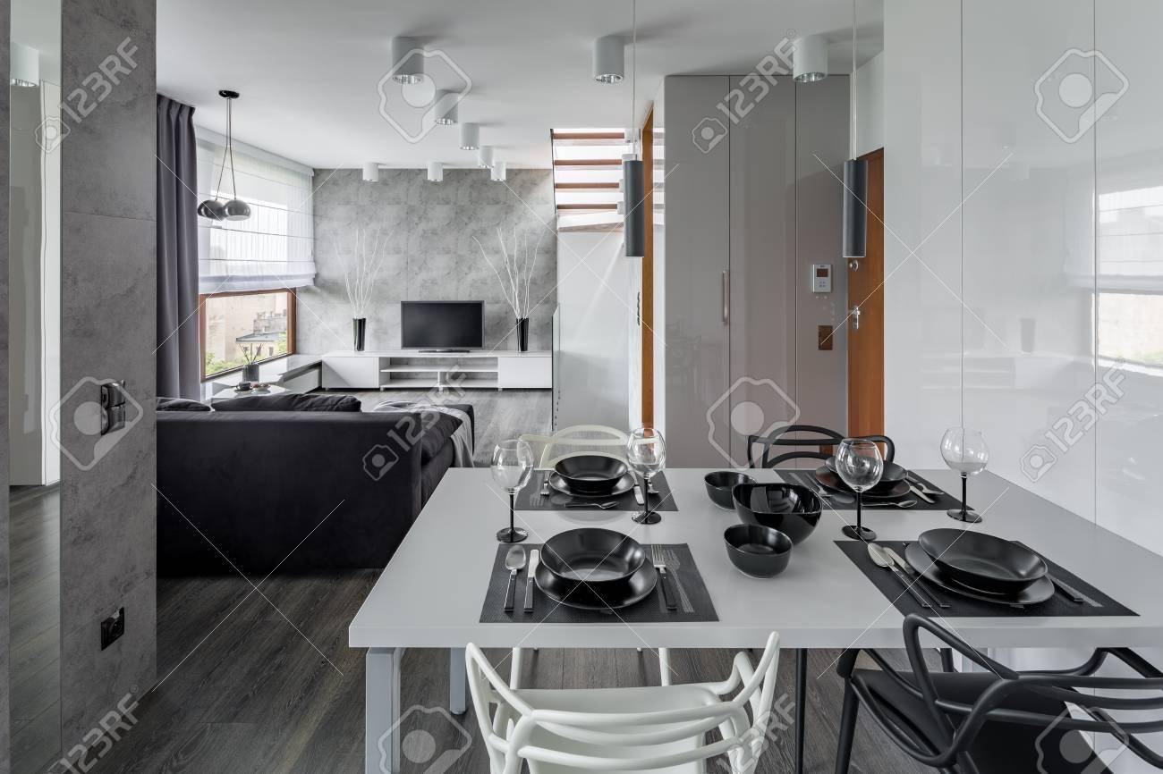 Appartement moderne en gris et blanc avec table à manger blanche