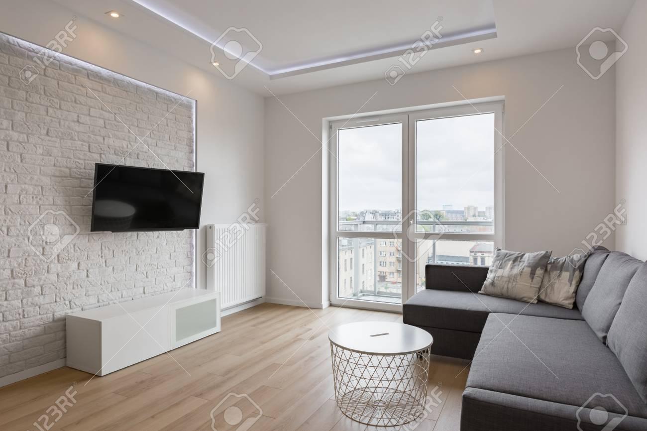 Living Room With Tv, Sofa, Balcony And White Brick Wall Stock Photo ...