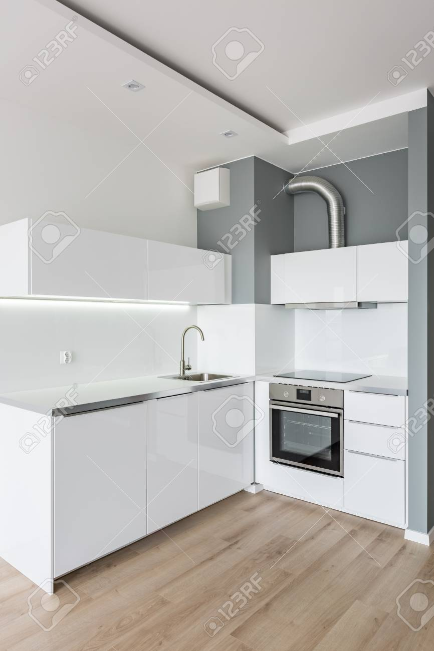 Small, modern, white kitchen with wooden floor panels