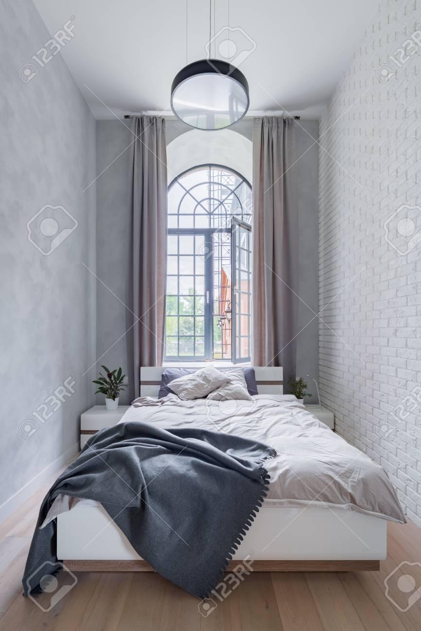 chambre loft avec lit double, grande fenêtre et mur de briques