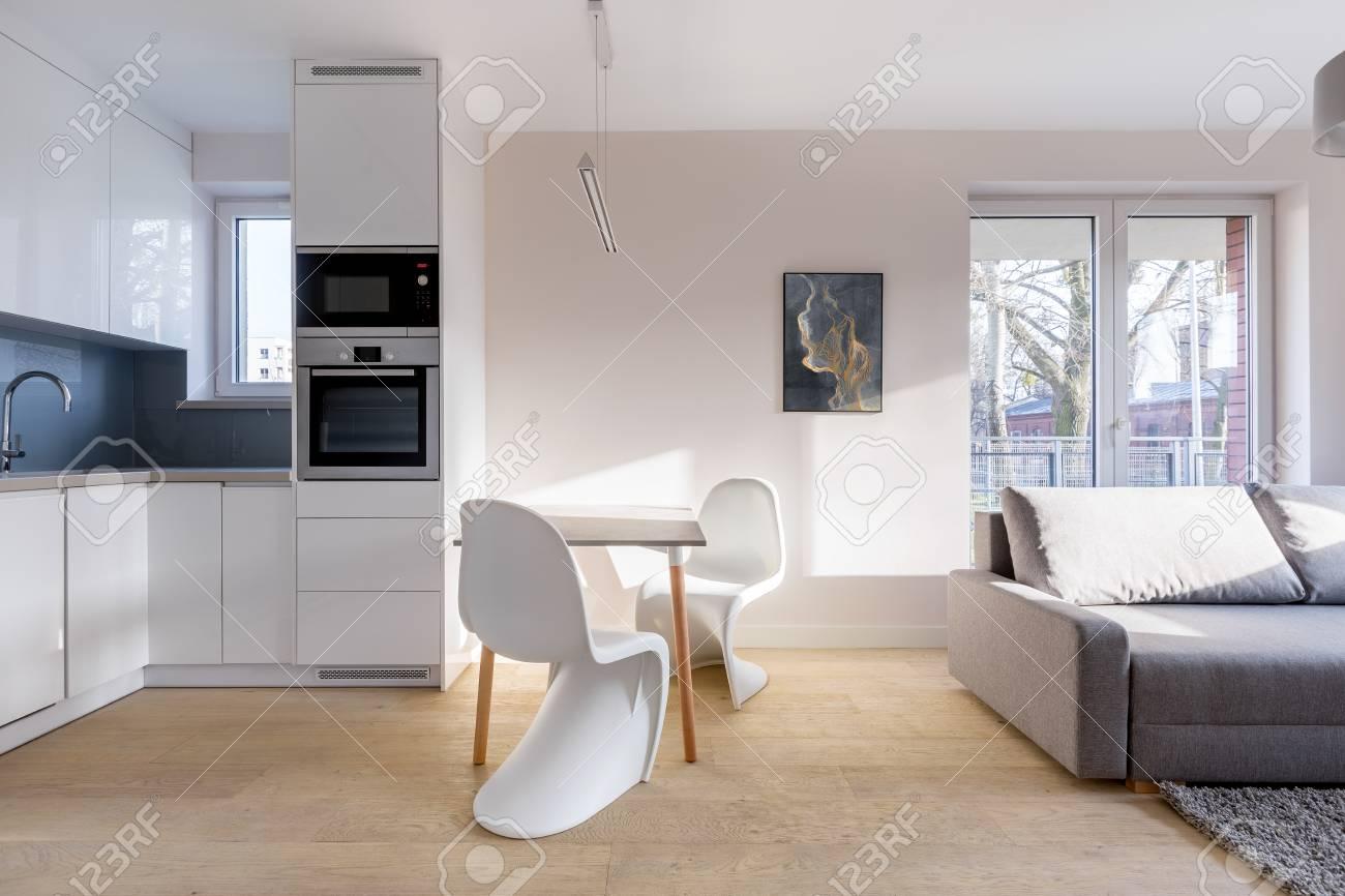 Einfache Wohneinrichtung Mit Offener Küche, Tisch Und Couch ...
