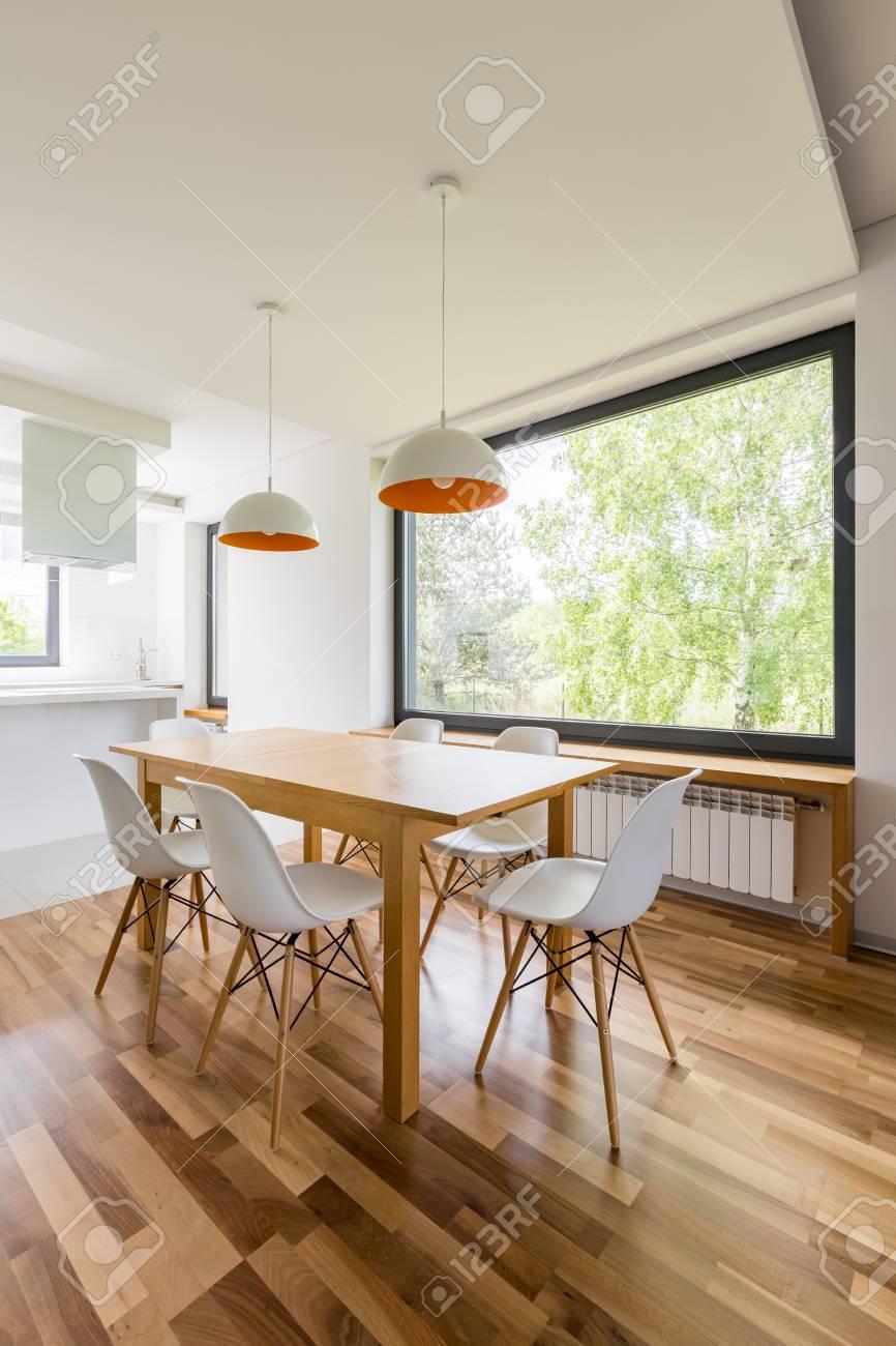 Nuevo diseño interior con mesa de comedor de madera, sillas blancas y  ventana grande.