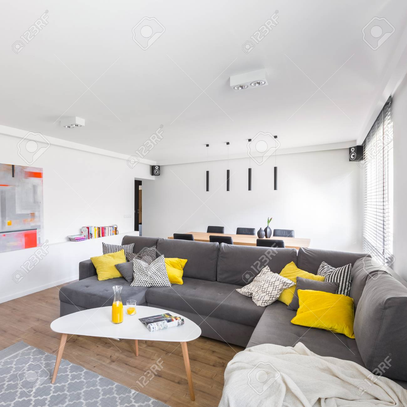 Salon moderne et blanc avec un très grand canapé gris et une table élégante
