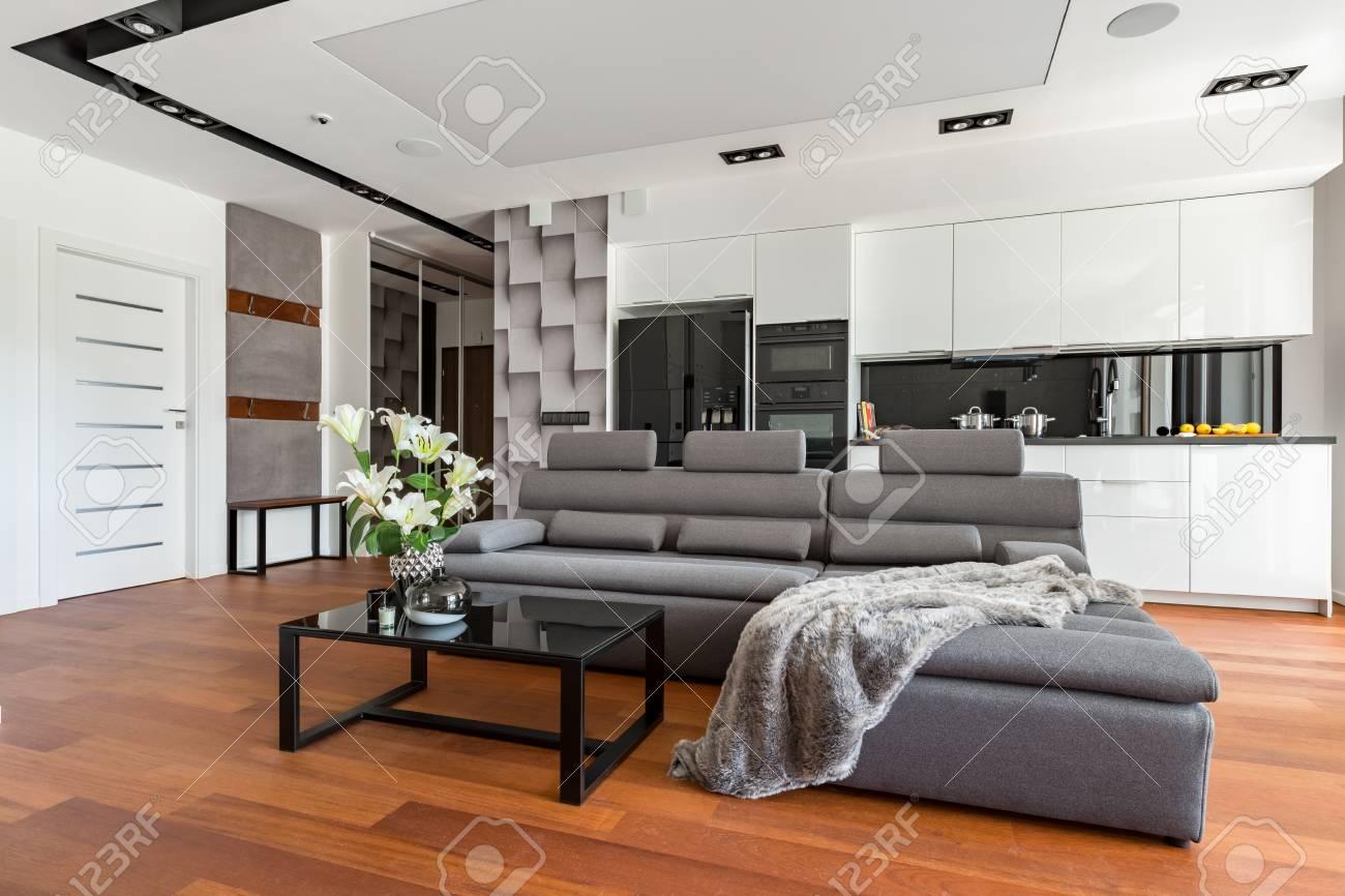 Soggiorno moderno con tavolino nero, divano e cucina a vista