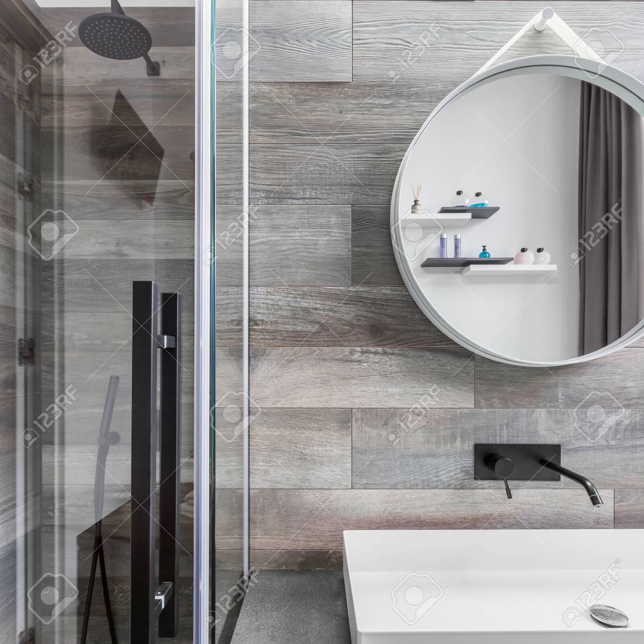 Cuarto de baño con plato de ducha, lavabo encimera y azulejos efecto madera