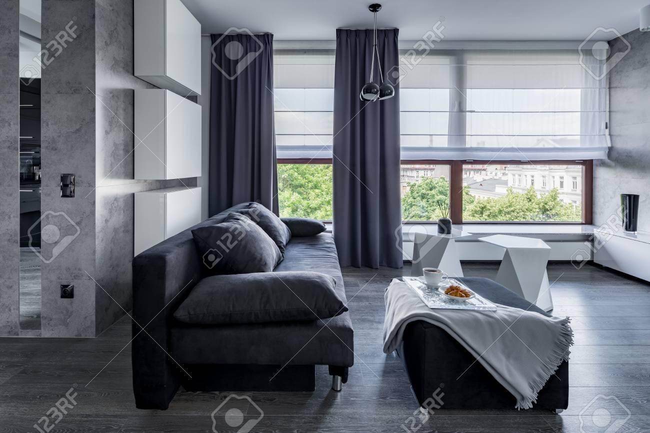 Gray living room with sofa, pouf coffee table and big windows..