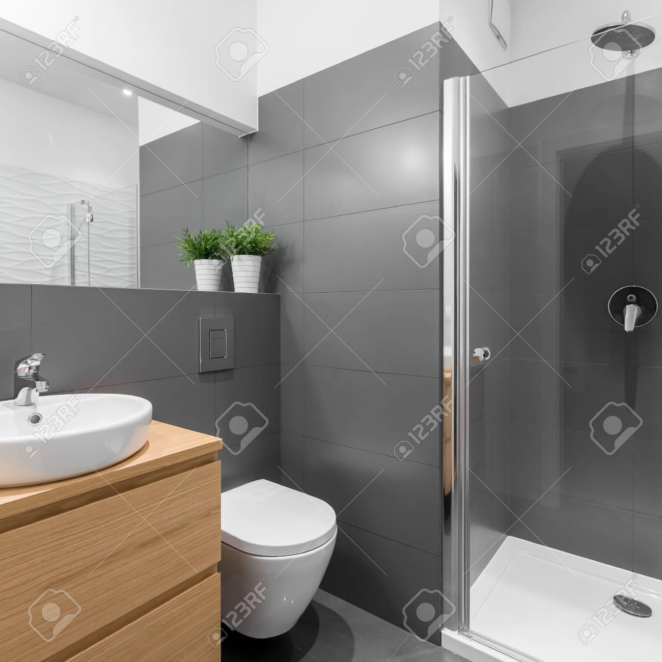 Elegantes Graues Badezimmer Mit Großer Dusche Und Holzmöbeln ...