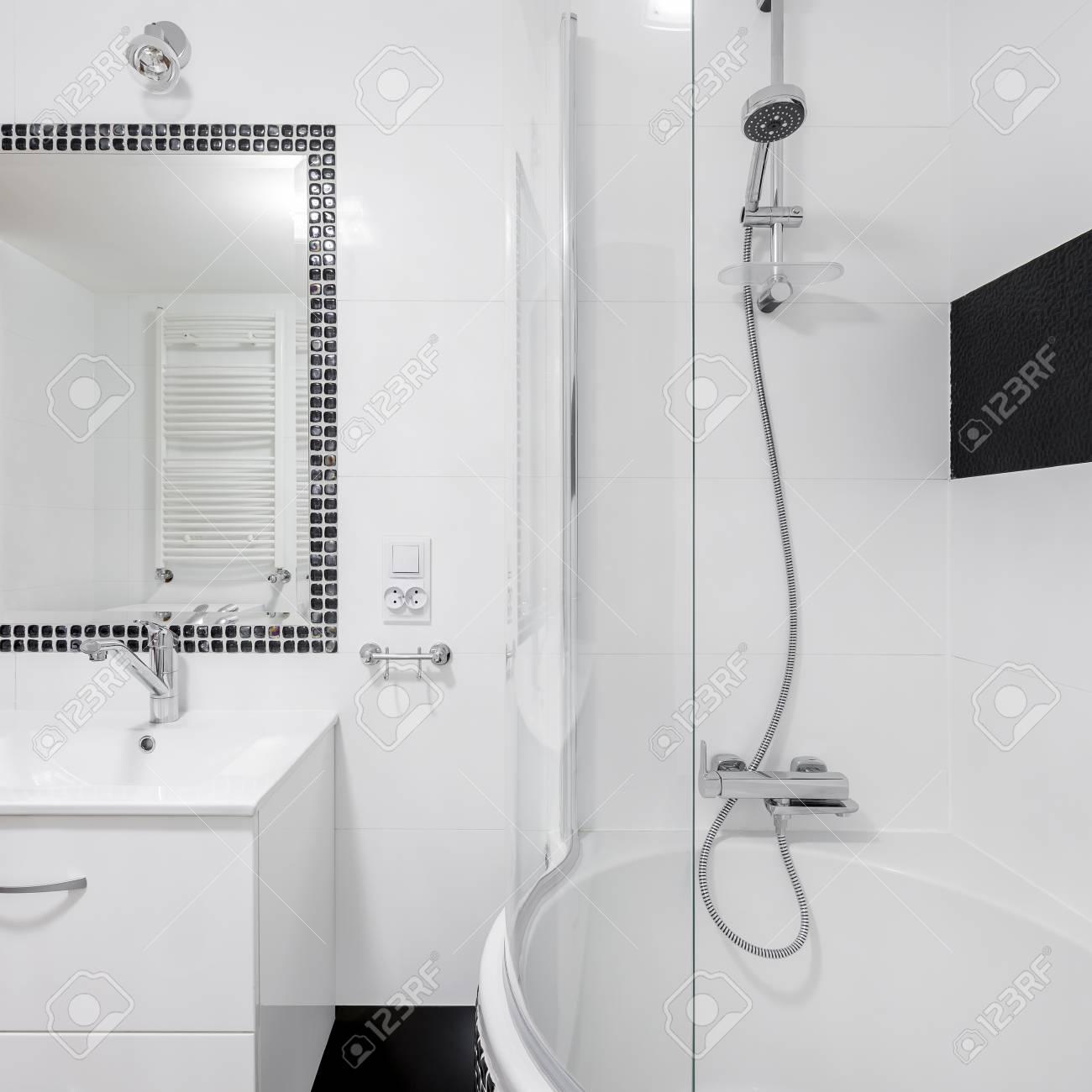 Intérieur de salle de bain de luxe blanc avec grand miroir, robinet et  baignoire avec douche