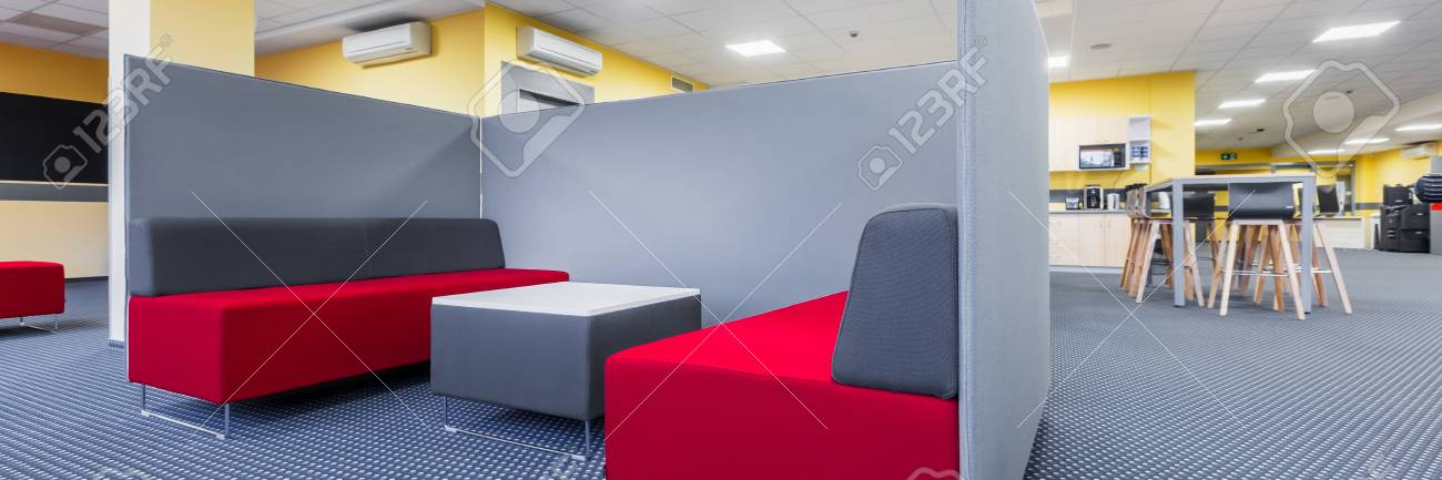 Superior Panorama Of Library Lounge Area With Red Sofa, Table And Grey Partition  Stock Photo