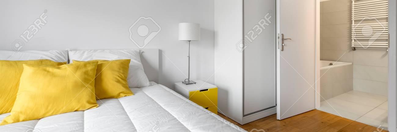 Moderna camera da letto bianca con armadio e bagno privato, panorama