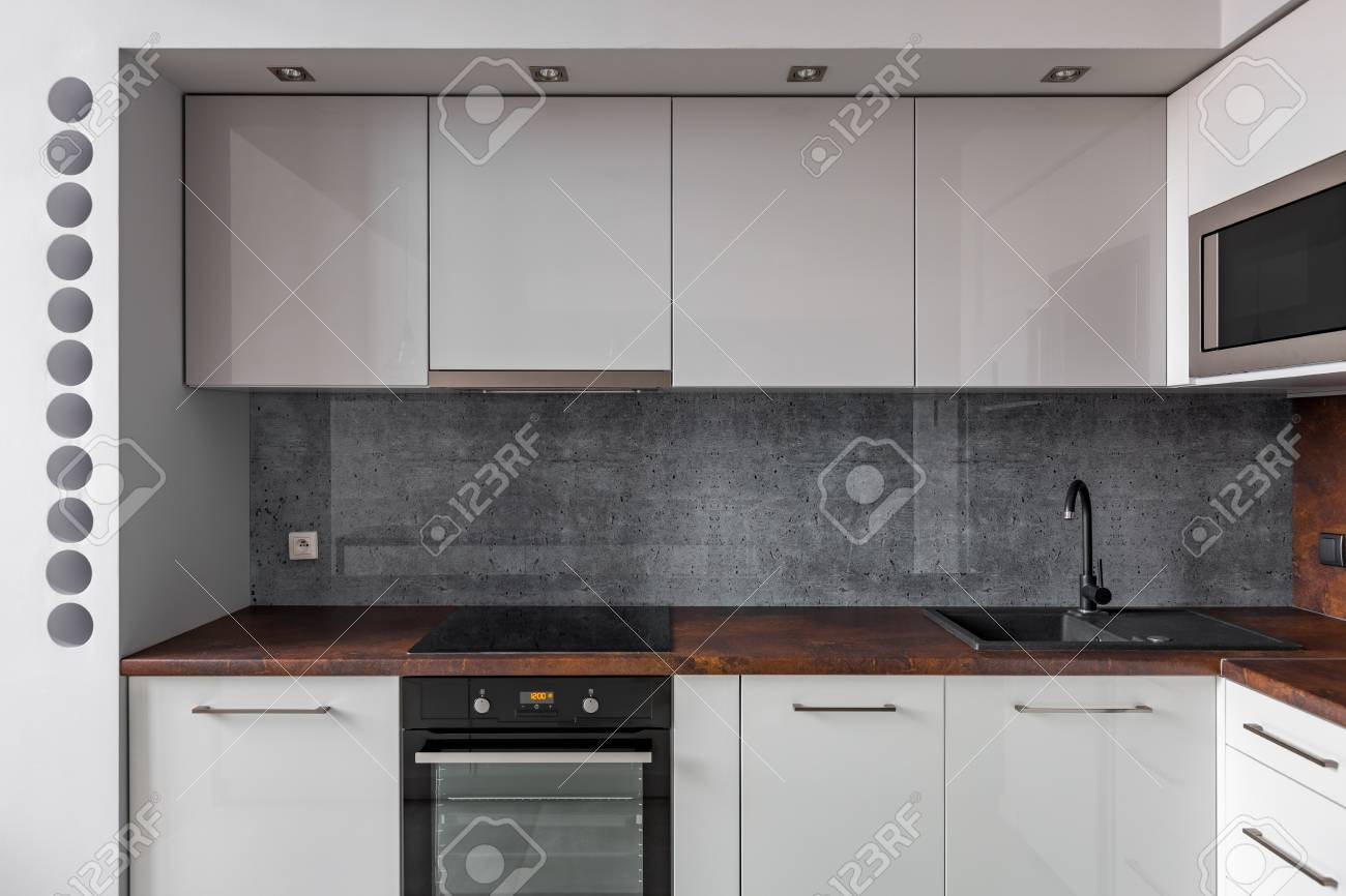 - Modern Kitchen With Granite Backsplash And Functional Cabinets