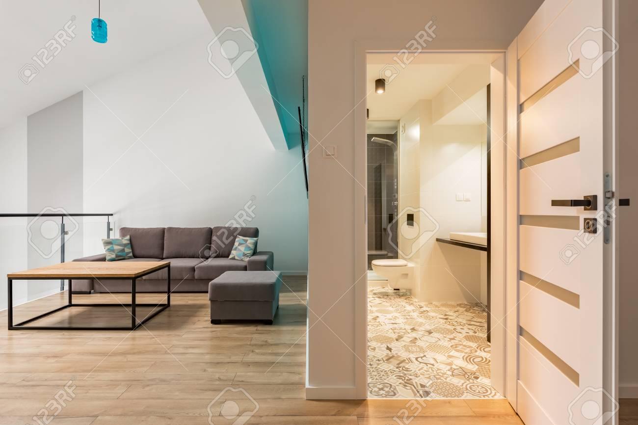Chambre Ouverte Salle De Bain chambre avec table en bois, canapé et porte ouverte sur la salle de bain