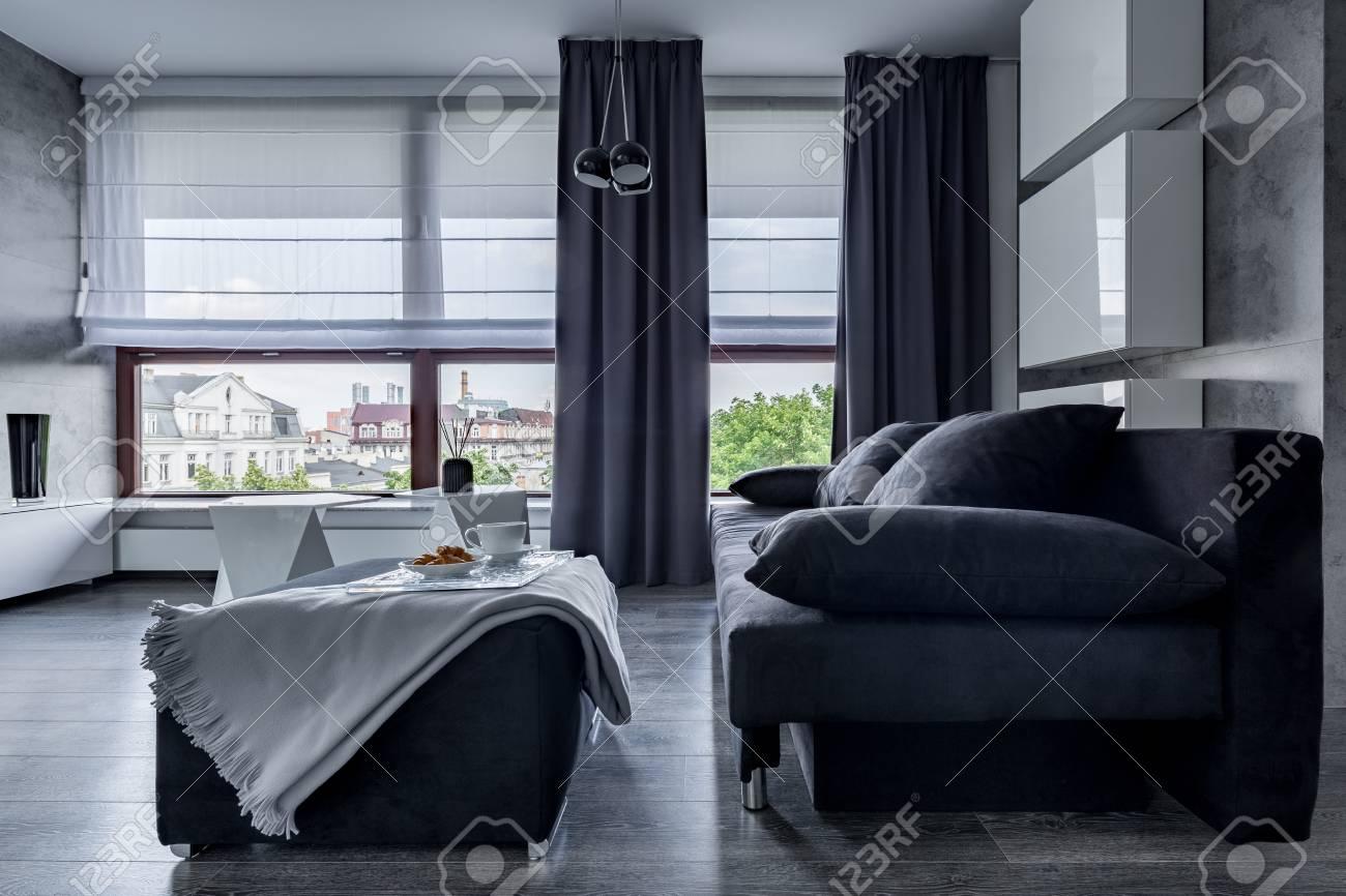 Modernes Wohnzimmer Mit Grauer Couch Hocker Und Grossen Fenstern