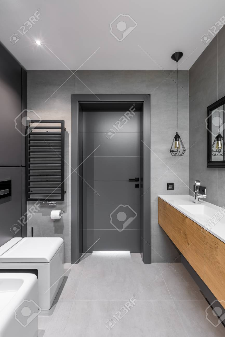 Cubic Toilet And Wooden Cabinets In Bathroom With Gray Walls Stock Photo Picture And Royalty Free Image Image 92164742