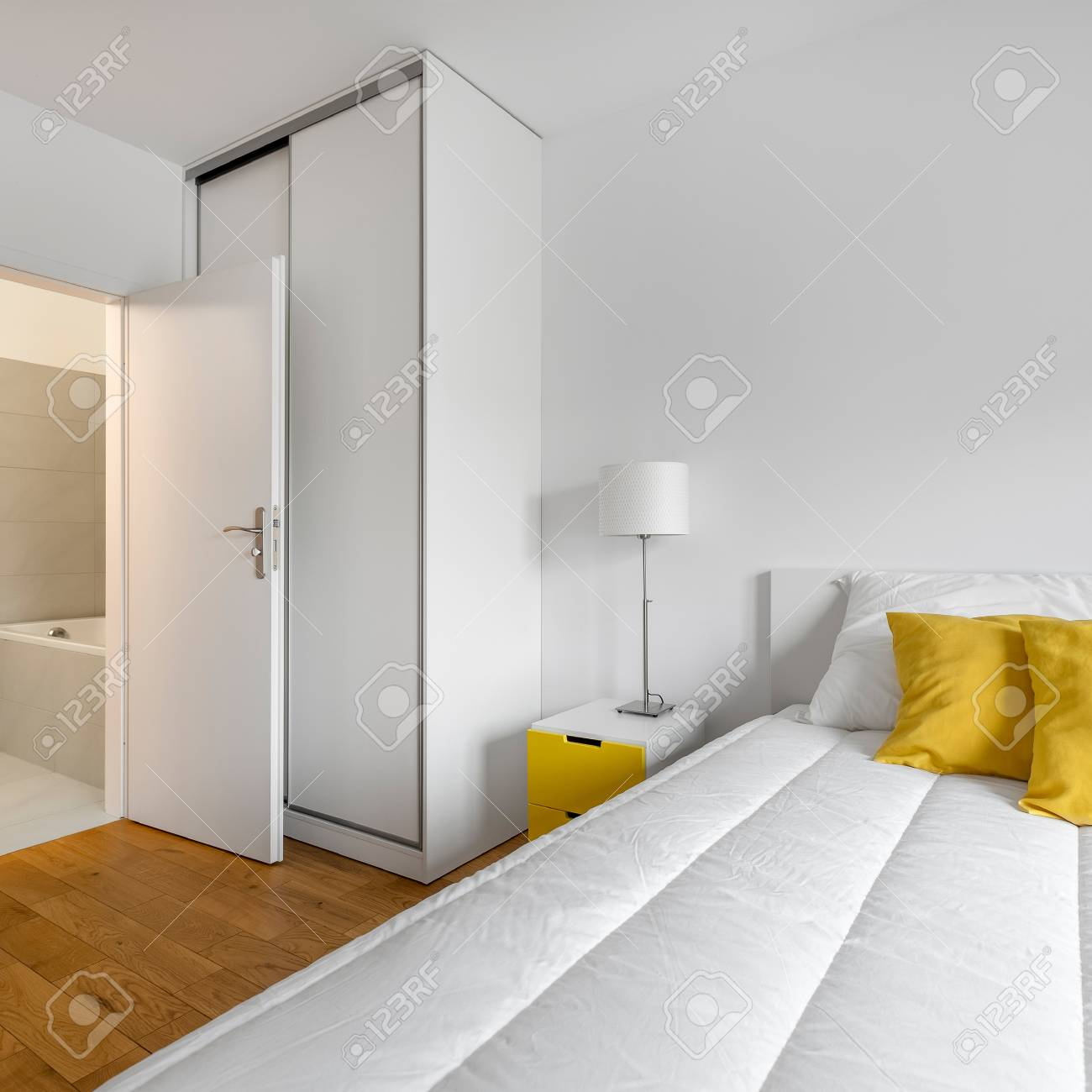 Modern, white bedroom with big bed, closet and private bathroom