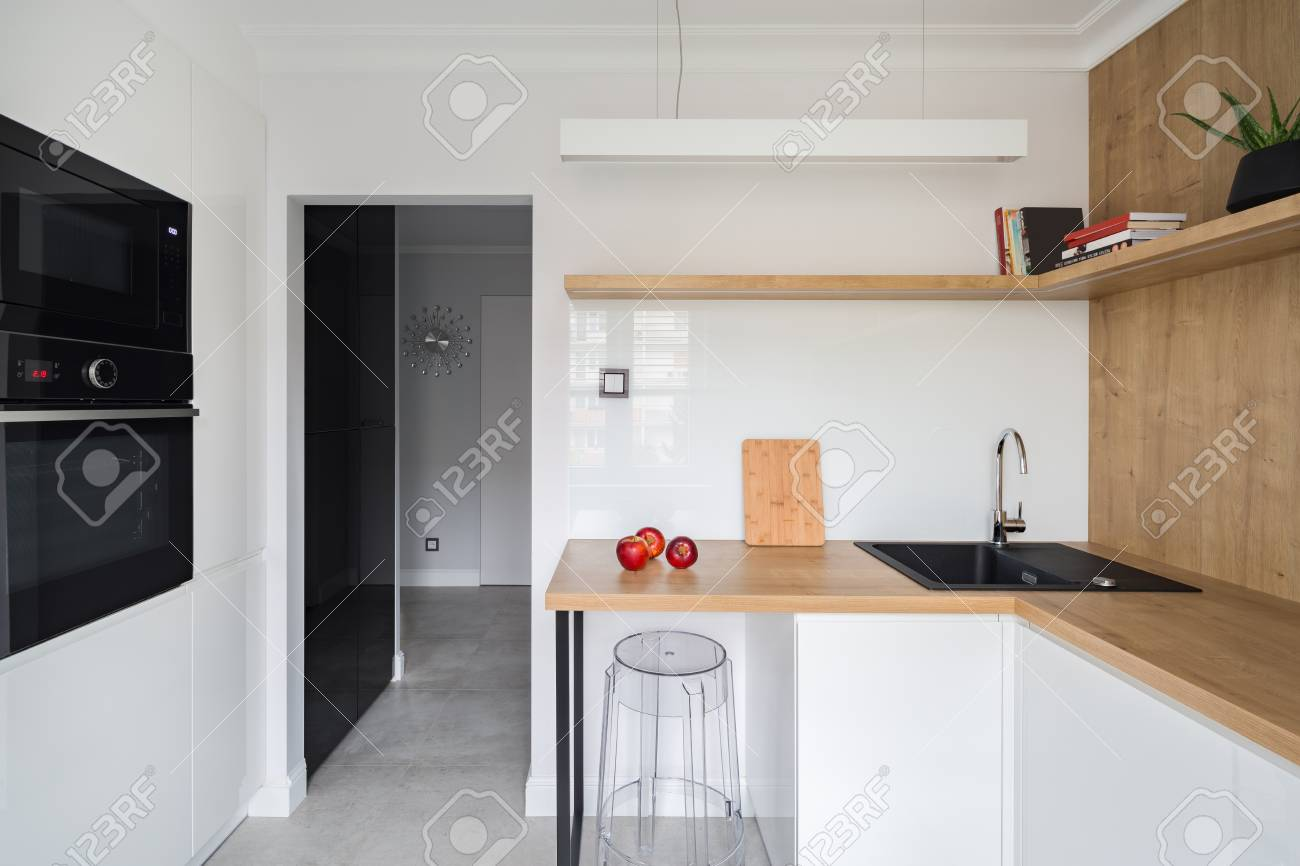 Modern, white kitchen with wooden worktop and transparent chair
