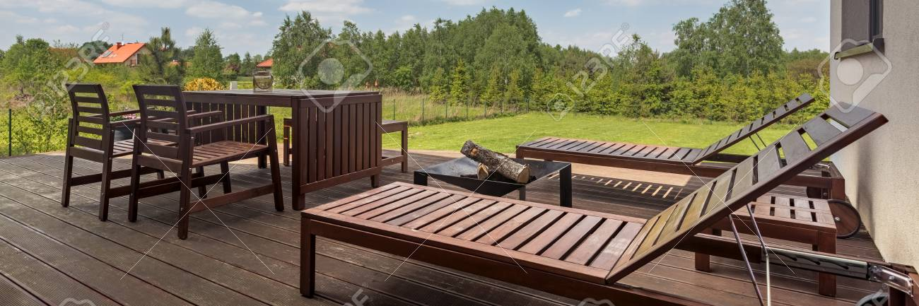 Modern villa patio with wooden decking and outdoor furniture..