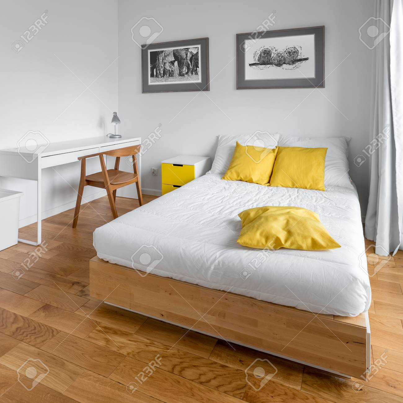 Modern White Bedroom With Big Wooden Bed Desk And Yellow Decorations Stock Photo Picture And Royalty Free Image Image 97351354