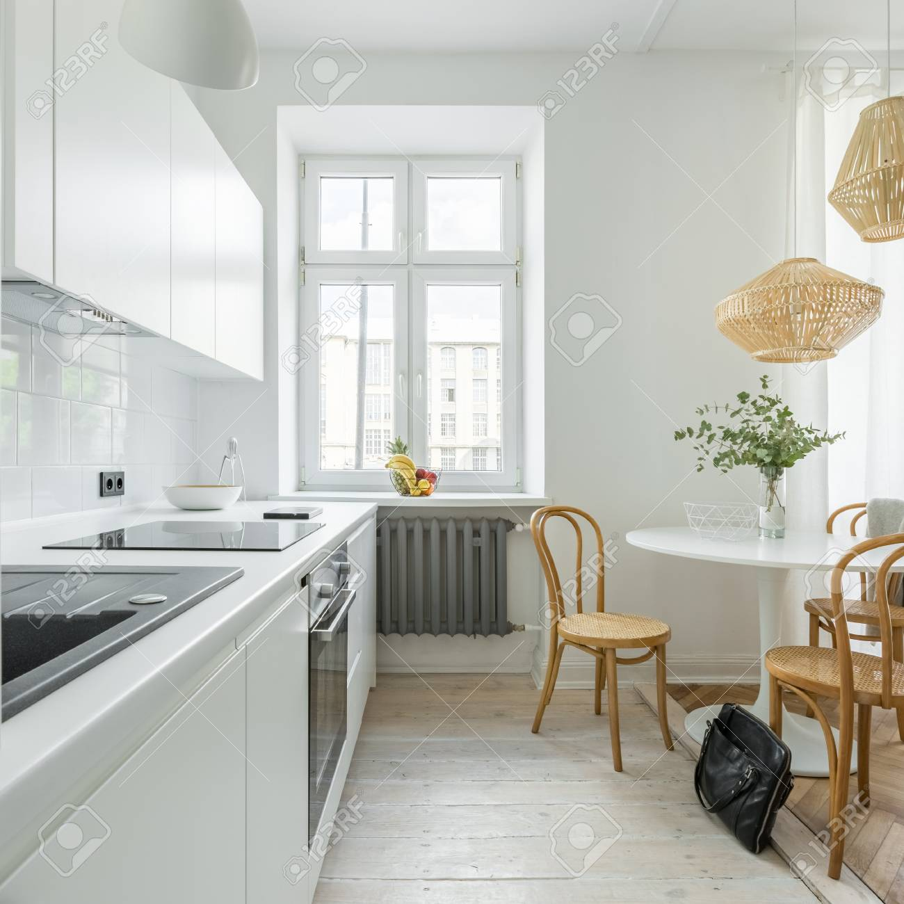Table And Cane Chairs In Kitchen Decorated With Wooden Lamps Stock Photo Picture And Royalty Free Image Image 99468567