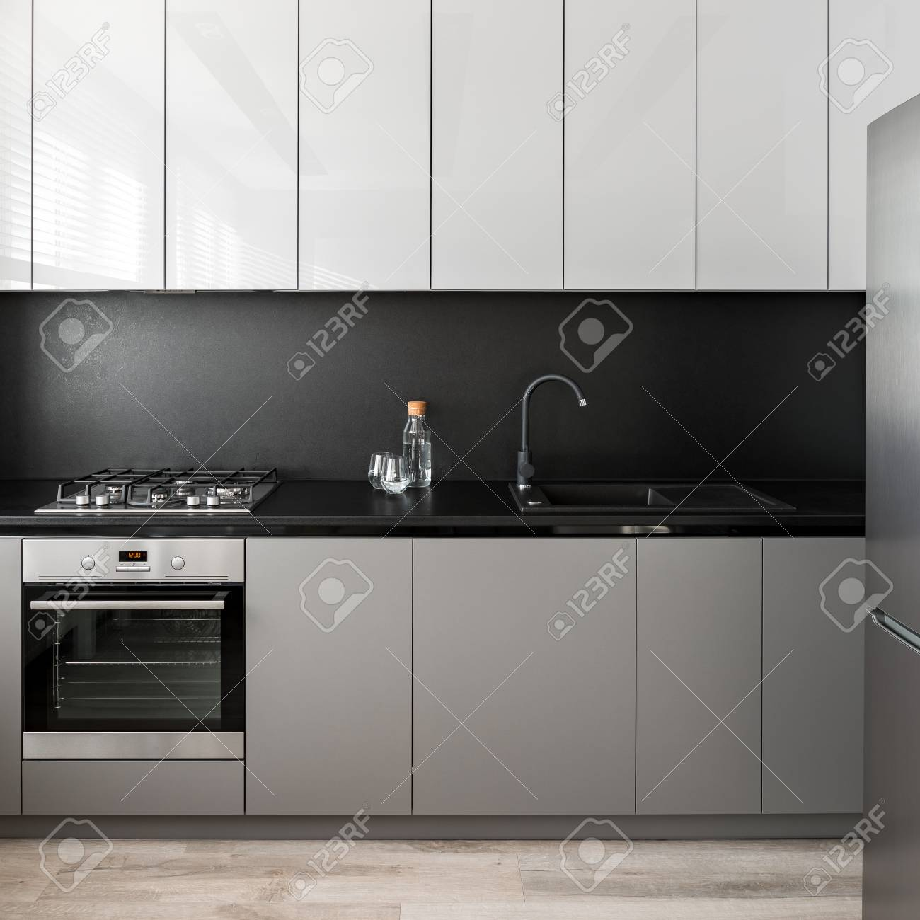 - Simple Kitchen Unit In Gray And White With Black Backsplash Stock