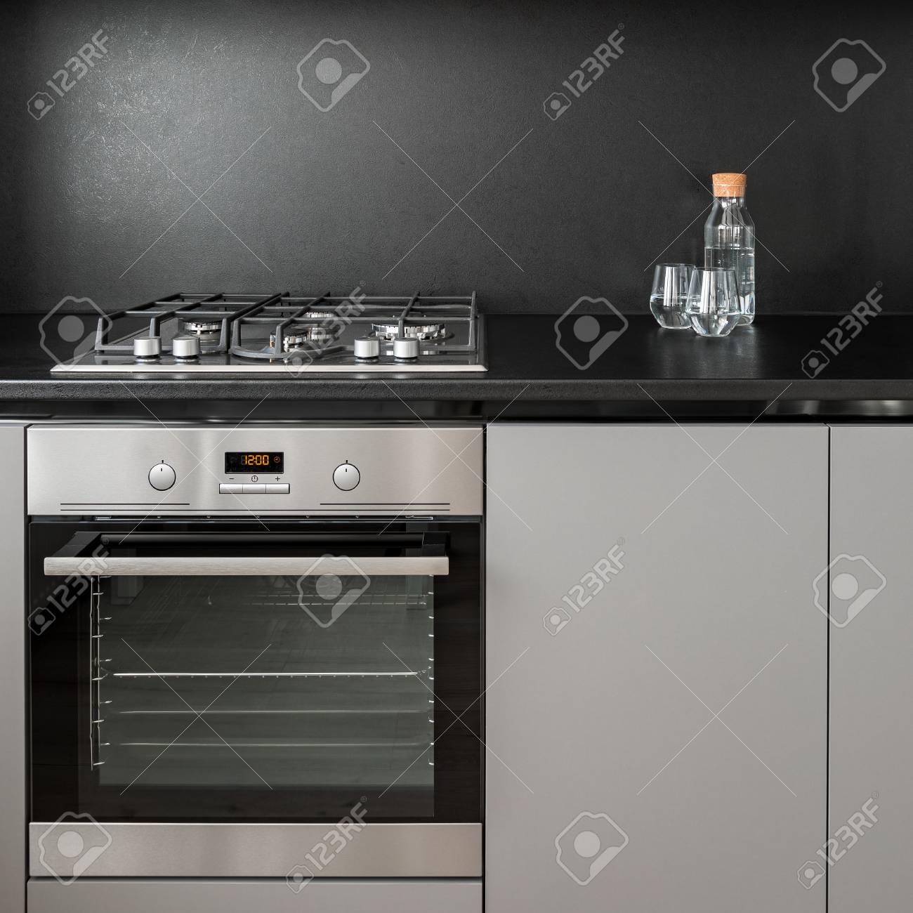 - Gray Kitchen Cabinet, Black Backsplash, Oven And Hob Stock Photo