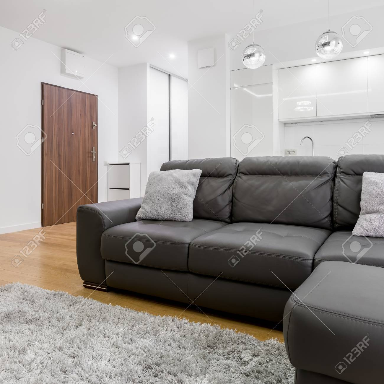 Living room with big black leather sofa in modern flat