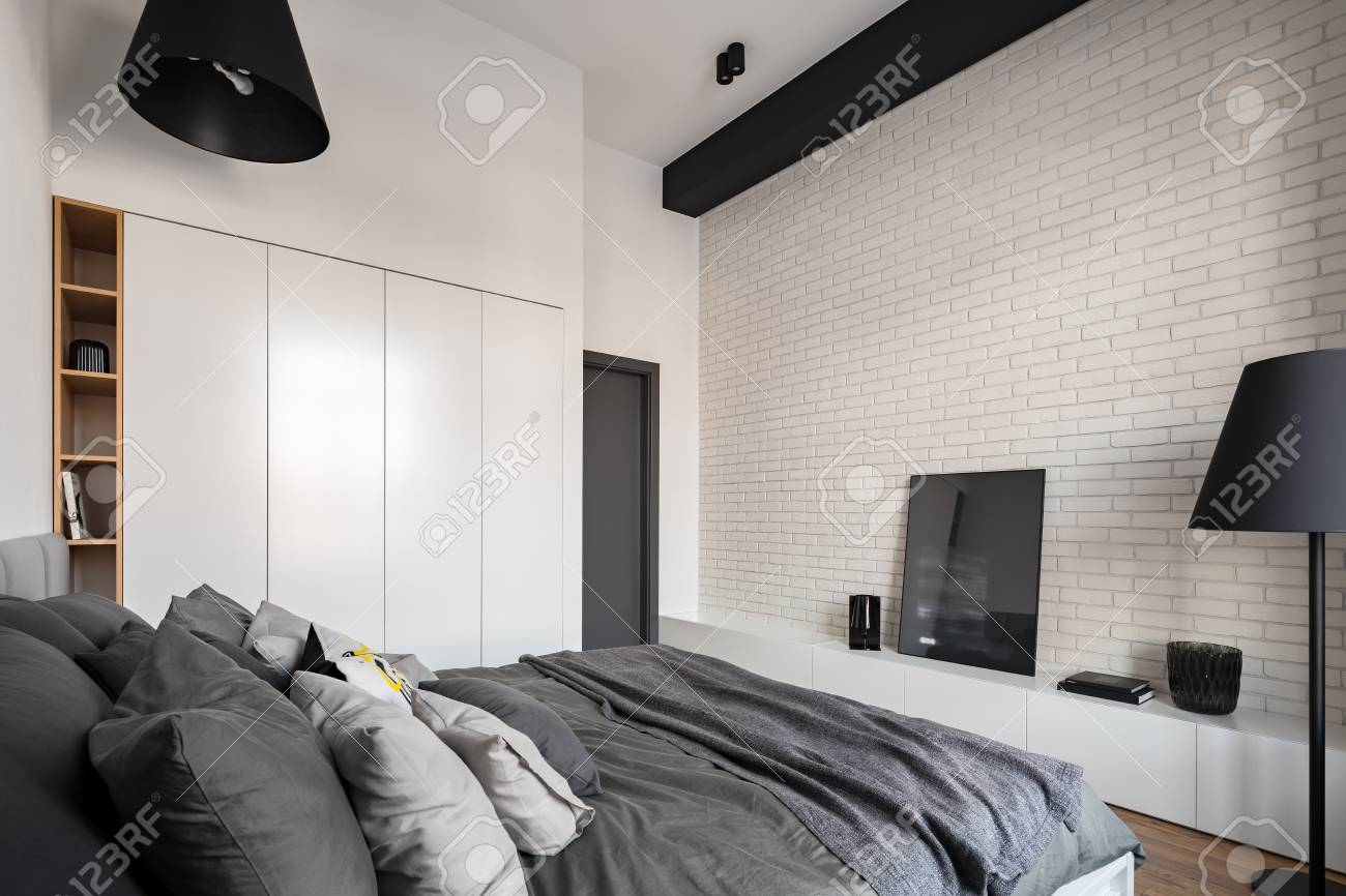 Contemporary white bedroom with brick wall, big wardrobe and..