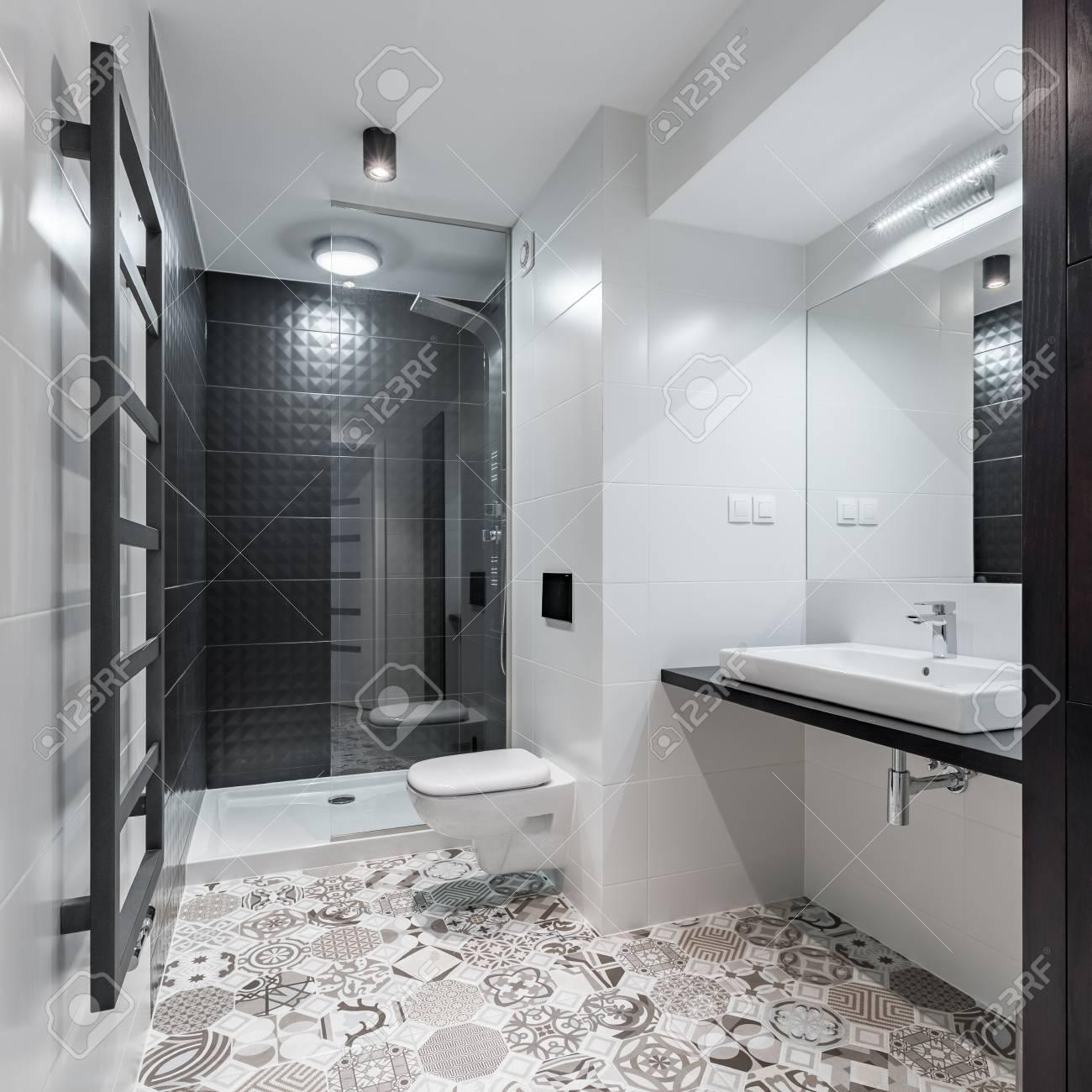 Cuarto de baño blanco y negro con ducha y azulejos de azulejos antiguos