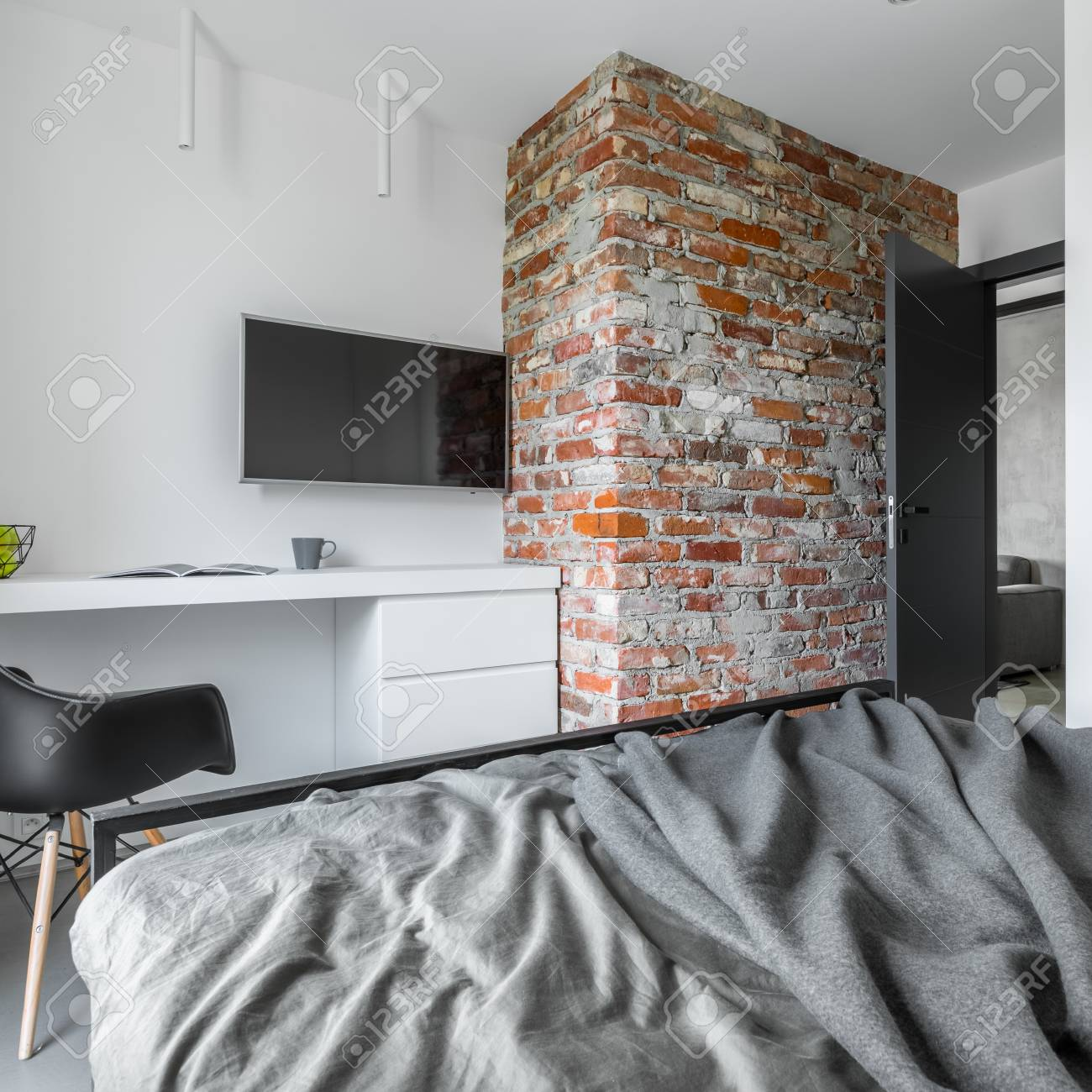 Bedroom with big bed, brick wall, desk and black chair
