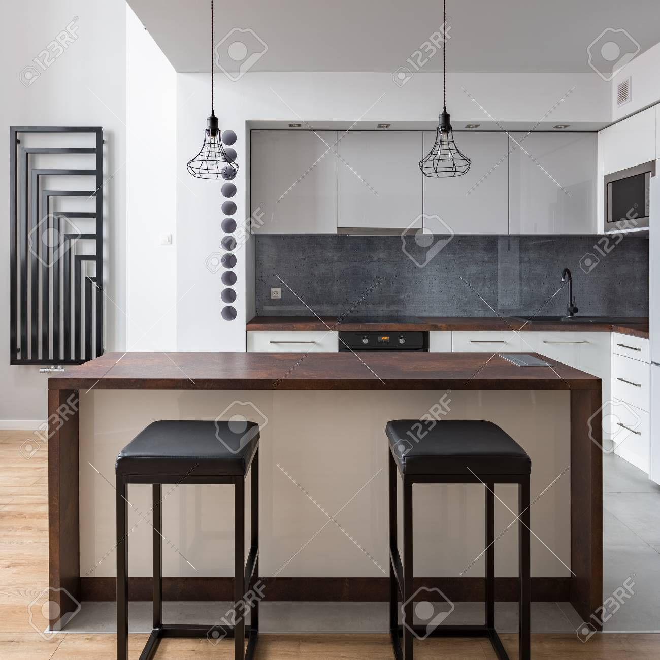 Modern Open Kitchen With Table Stools And Decorative Wall Radiator Stock Photo Picture And Royalty Free Image Image 108426424