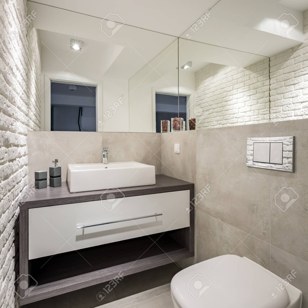 Modern Bathroom With Brick Wall Toilet And Basin Cabinet Stock