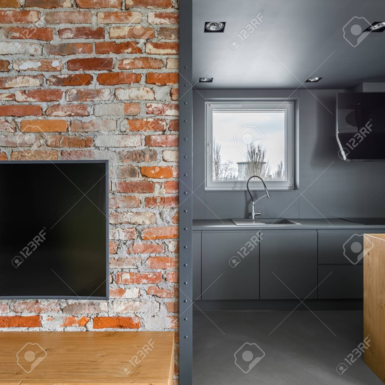 Brick wall with entrance to the kitchen in loft apartment