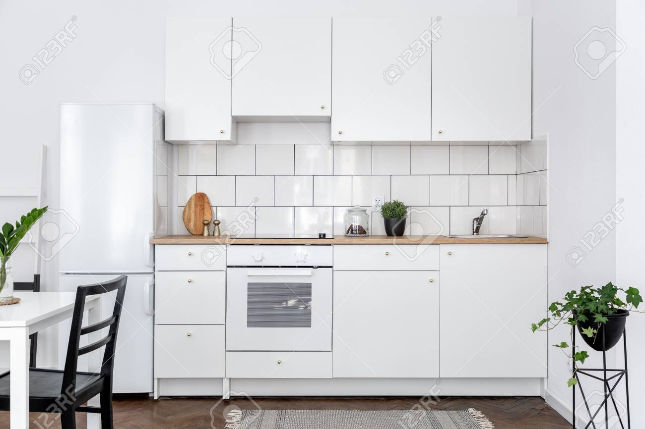 Contemporary kitchen with white cupboards and dining table with..