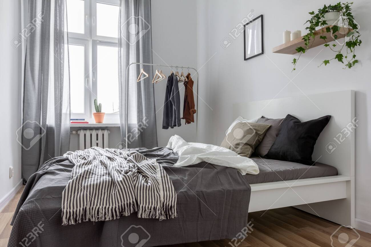 Contemporary bedroom with gray window curtains and clothes rack