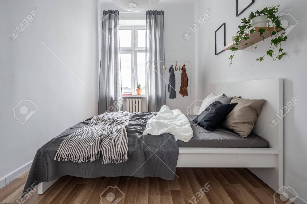 New Bedroom With Simple Bed Clothes Rack And Wall Shelf Stock Photo Picture And Royalty Free Image Image 119653490
