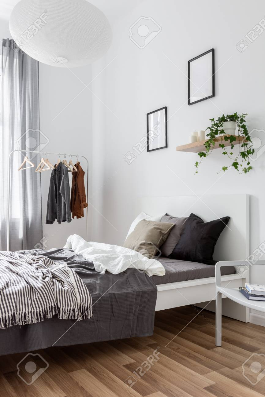 Simple Bedroom With Single Bed Clothes Rack And Modern Pendant Stock Photo Picture And Royalty Free Image Image 119654110