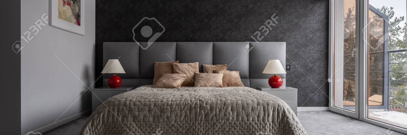 Contemporary bedroom with double bed, black wallpaper and balcony,..
