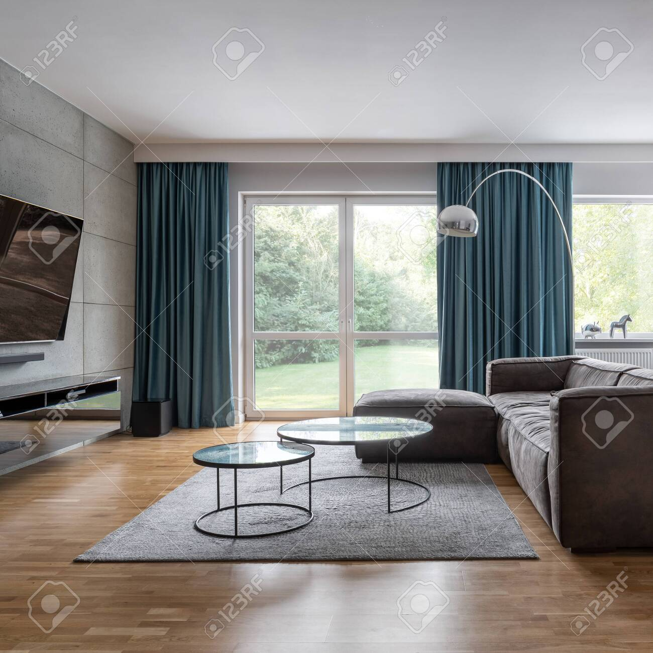 Modern living room with big windows, cement wall and corner sofa