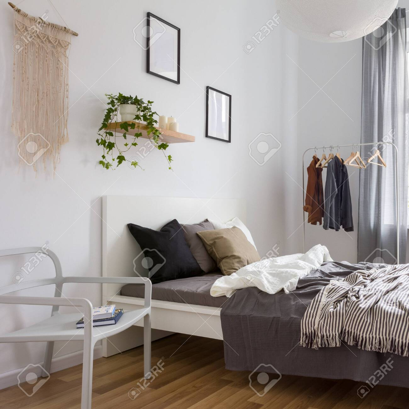 Simple Bedroom With Double Bed Clothes Rack And Wall Decoration