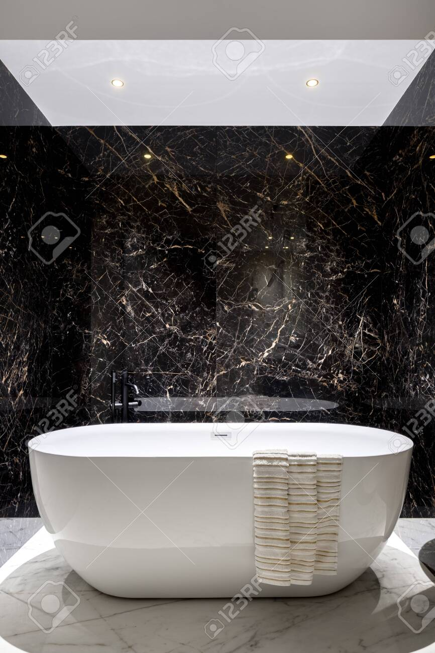 Luxury White Bathtub In Elegant Bathroom With Black Marble Tiles Stock Photo Picture And Royalty Free Image Image 137078975