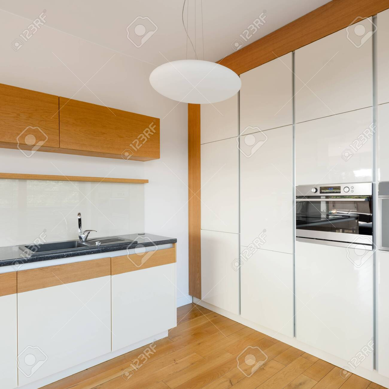 Modern white kitchen with stylish wooden floor, cupboards and..