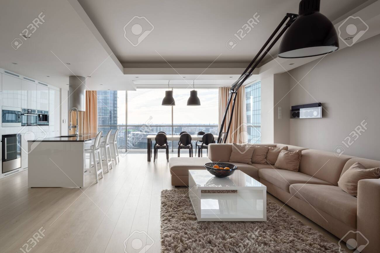 Modern and elegant apartment with big corner sofa, stylish black lamp, luxury kitchen area and dining table in one spacious room with big window and amazing city view - 150139287
