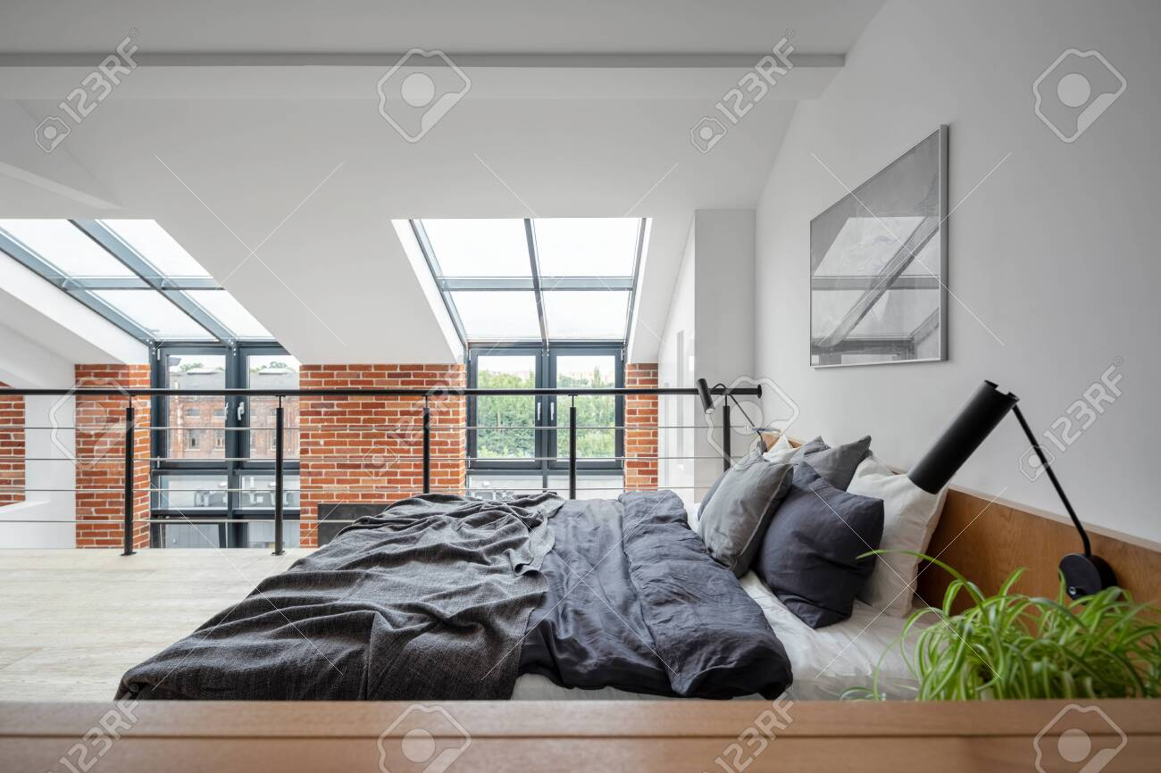 Simple bedroom on mezzanine in loft style apartment with big windows and exposed red brick on the wall - 152673688