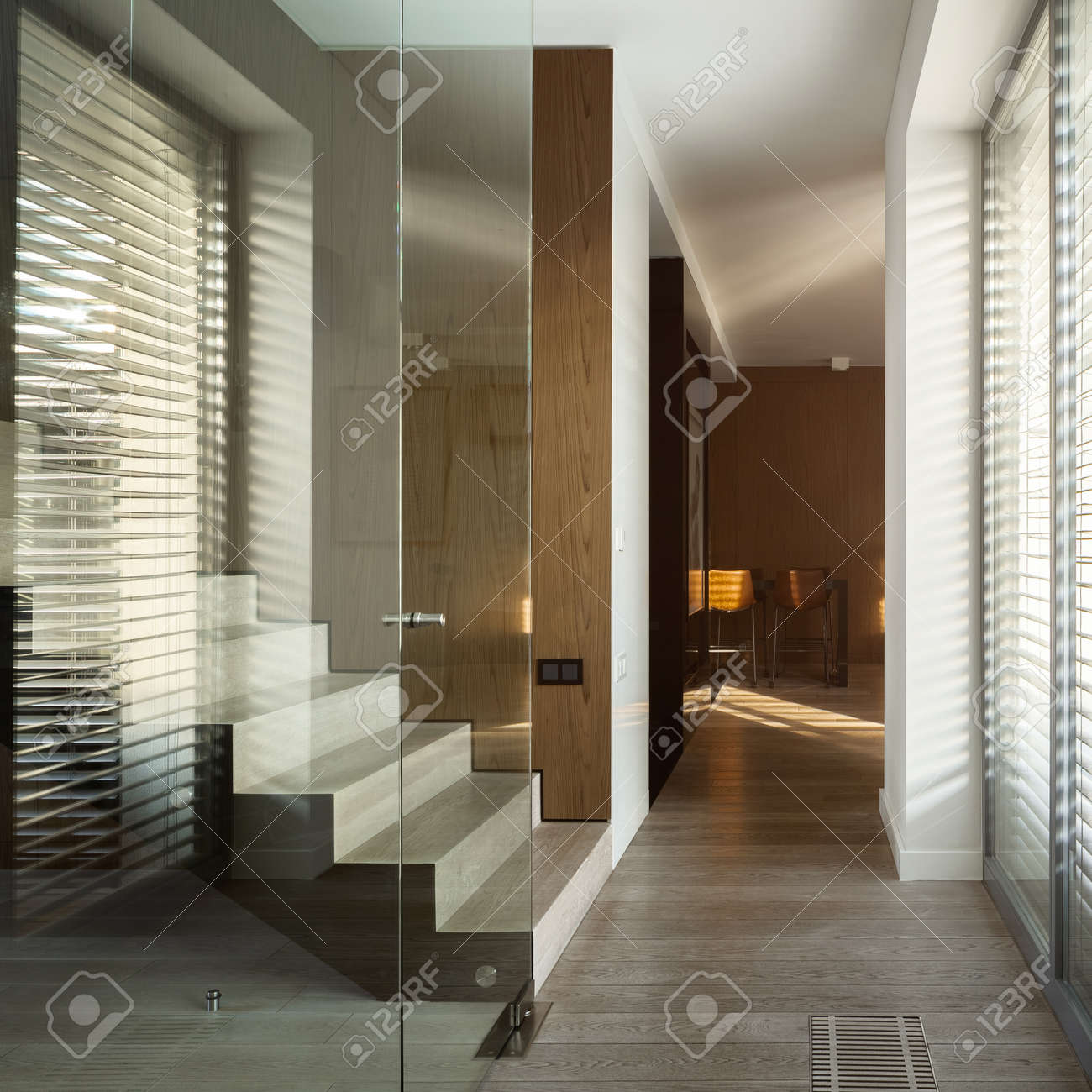 Modern wooden stairs behind glass wall in stylish home corridor with big window - 158294451